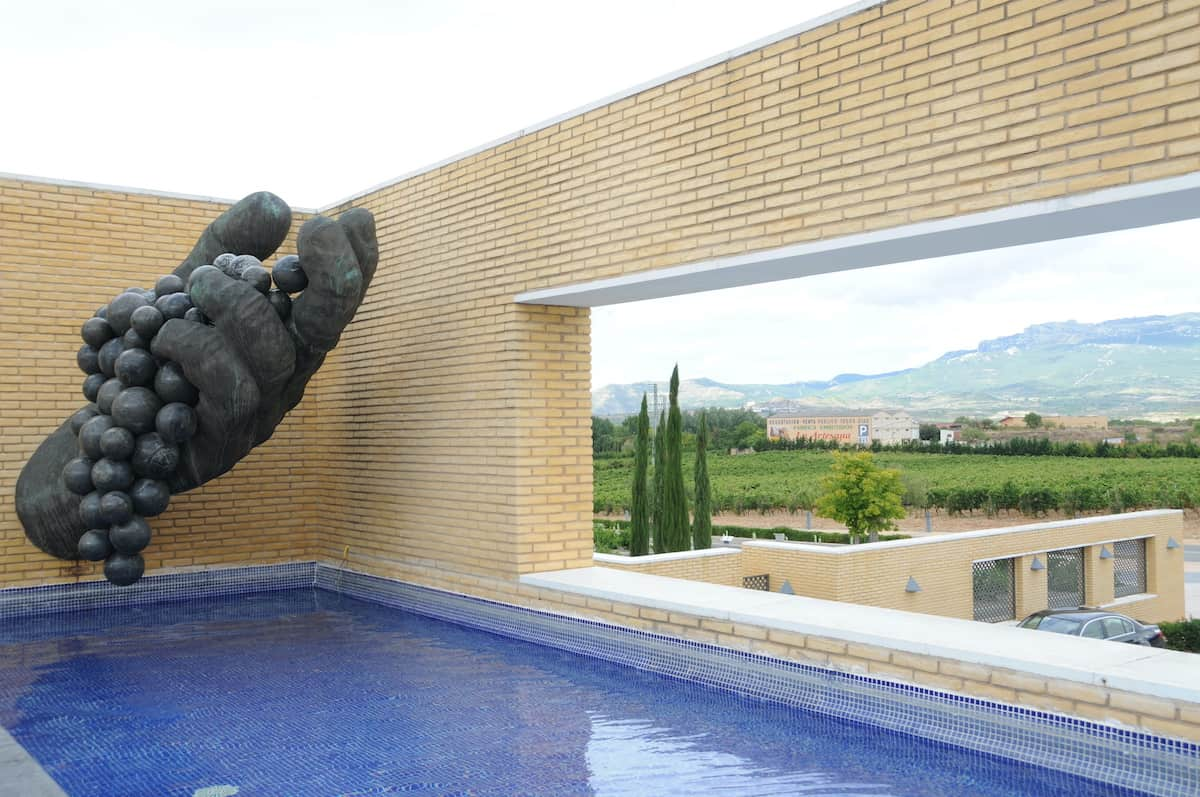 Small pool with a dark stone statue nearby and a window looking out over vineyards in the stone wall