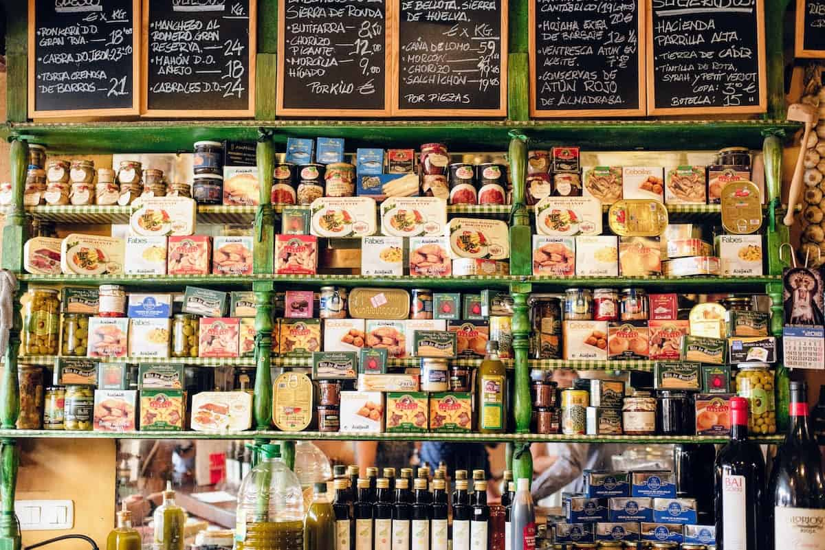 Full shelf of food items such as canned seafood at an old-fashioned Spanish grocery store