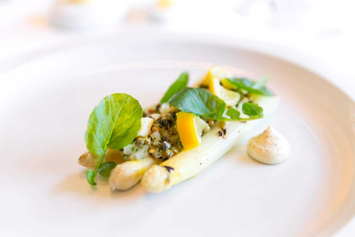 White asparagus garnished with lemon and herbs on a white plate.