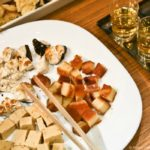 Different Turrón cut up on a white plate and served next to shot glasses of liquor.