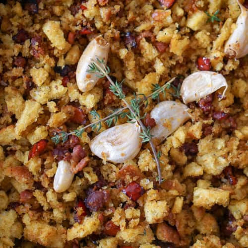 Migas con chorizo in a cast iron pan topped with garlic cloves and rosemary.