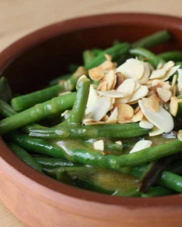 Green beans topped with slivered almonds in a small clay dish