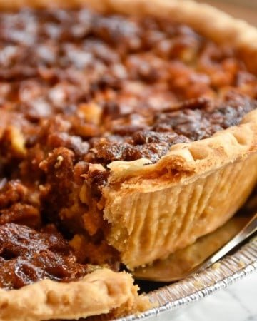 A slice of pecan pie being cut and lifted out of the pan