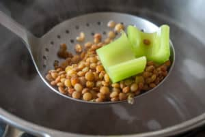 Spanish lentils in a slotted spoon with celery