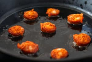 Chorizo frying in a cast iron skillet