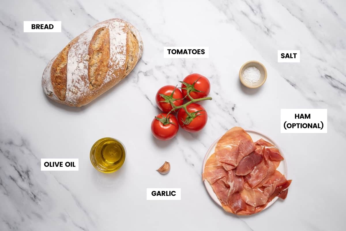 Ingredients for pan con tomate recipe on a white marble countertop