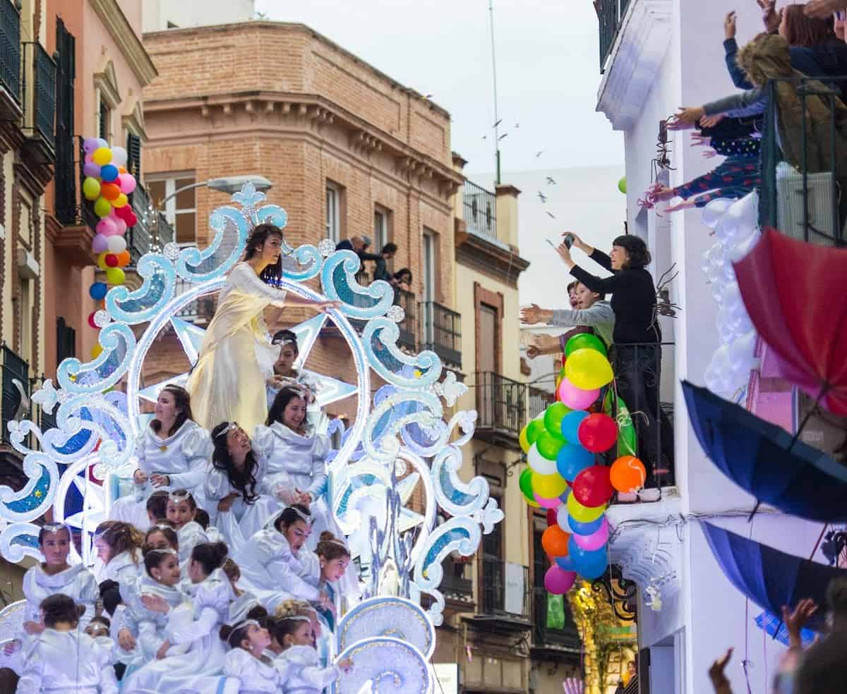 A float passes in front of a balcony with spectators during the Three Kings Day parade in Seville