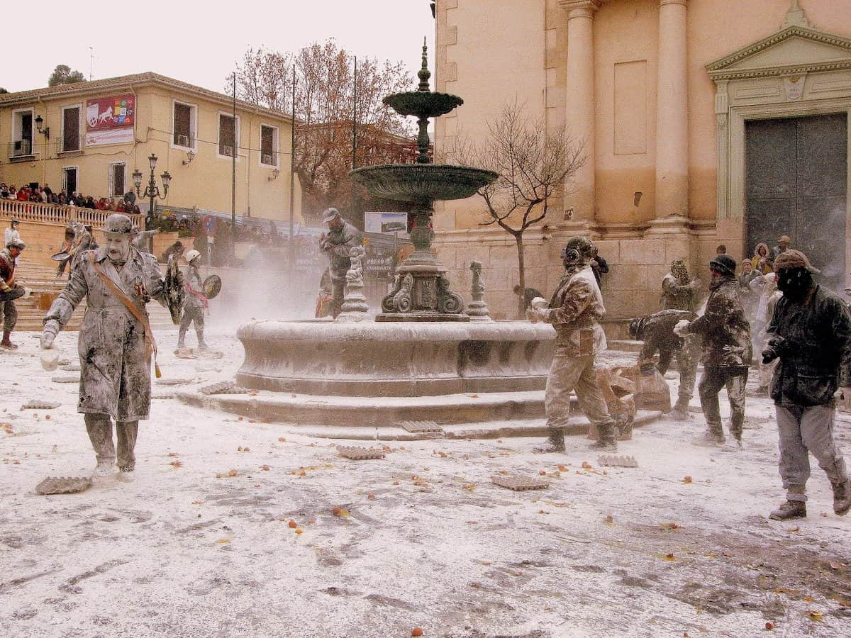 People throwing flour at one another in a plaza in Ibi, Spain during the Els Enfarinats festival
