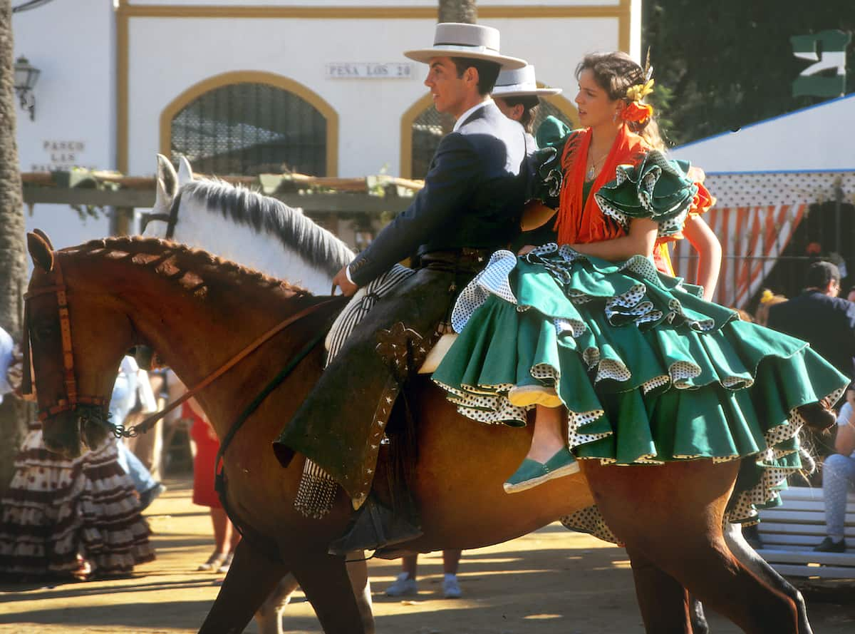 A couple in traditional Andalusian dress rides on horseback