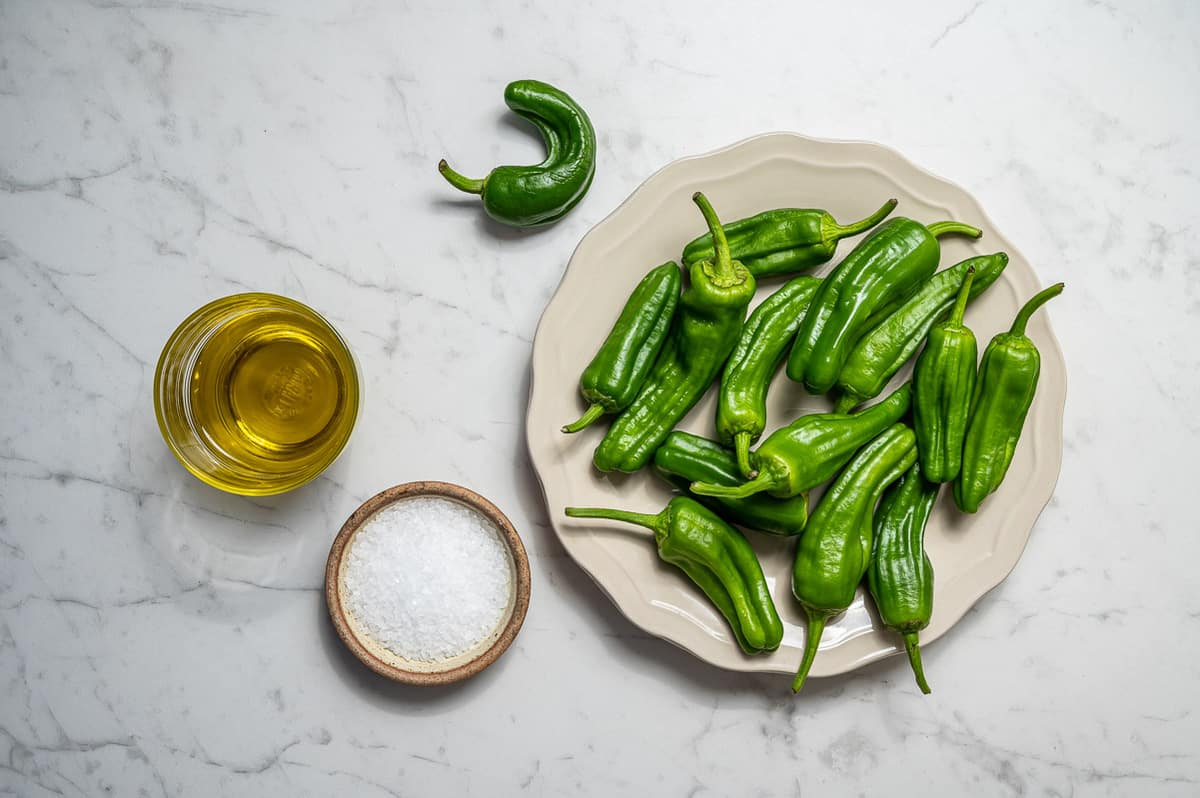 Ingredients for making padron peppers on a white marble counter. Cup of olive oil, sea salt and green padron peppers.