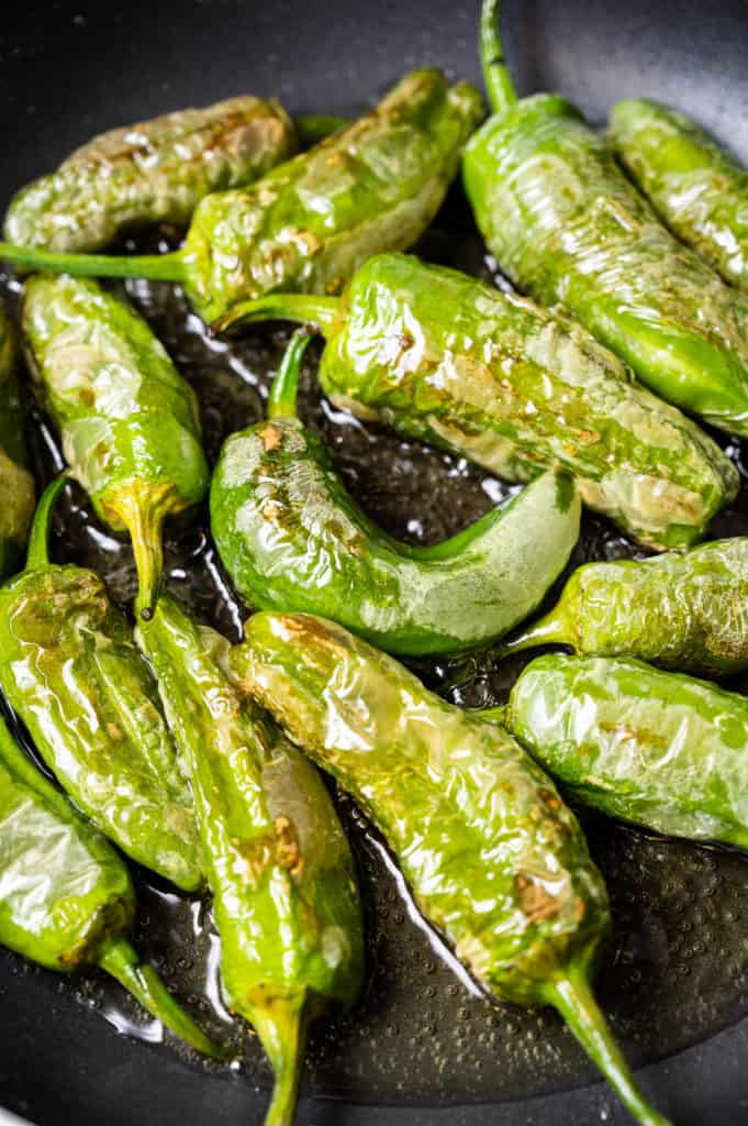 Padron peppers frying in a cast iron skillet