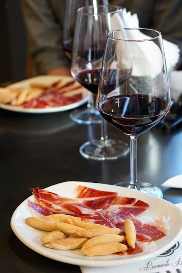 Enjoy some cured-to-perfection ham and a glass of local wine at Manzana de Oro, one of the best wine shops in Malaga!