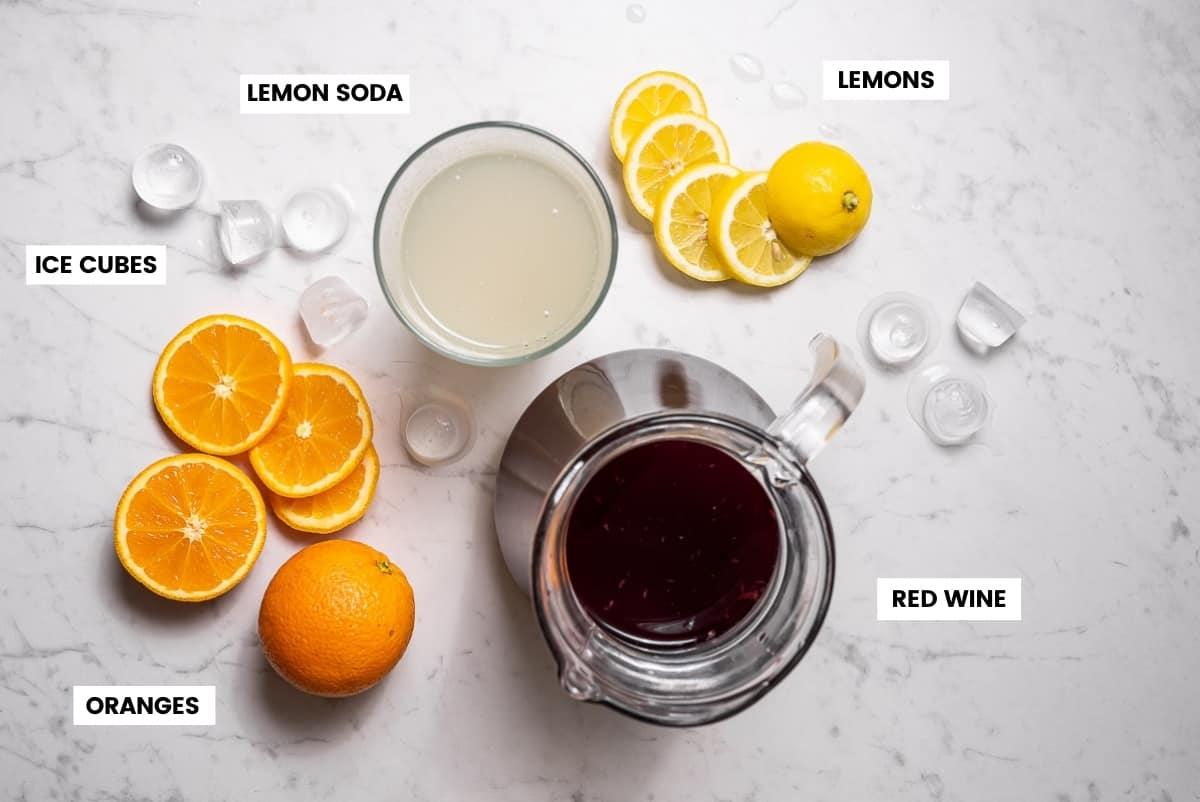 Ingredients to make tinto de verano on a white marble countertop