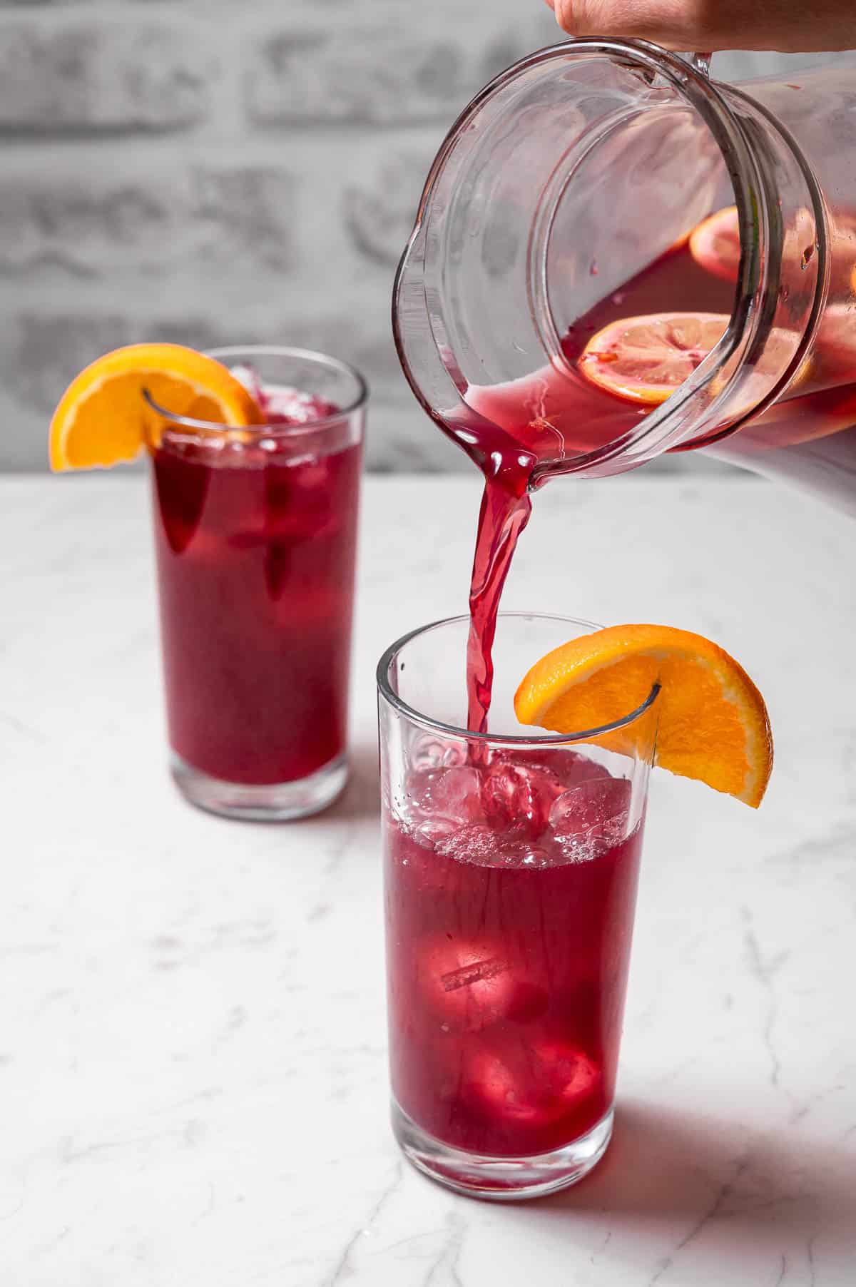Two tall glasses of Spanish tinto de verano and a clear pitcher pouring more into one of them.