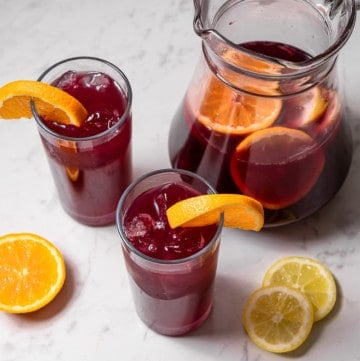 pitcher of tinto de verano with citrus fruit and two tall glasses