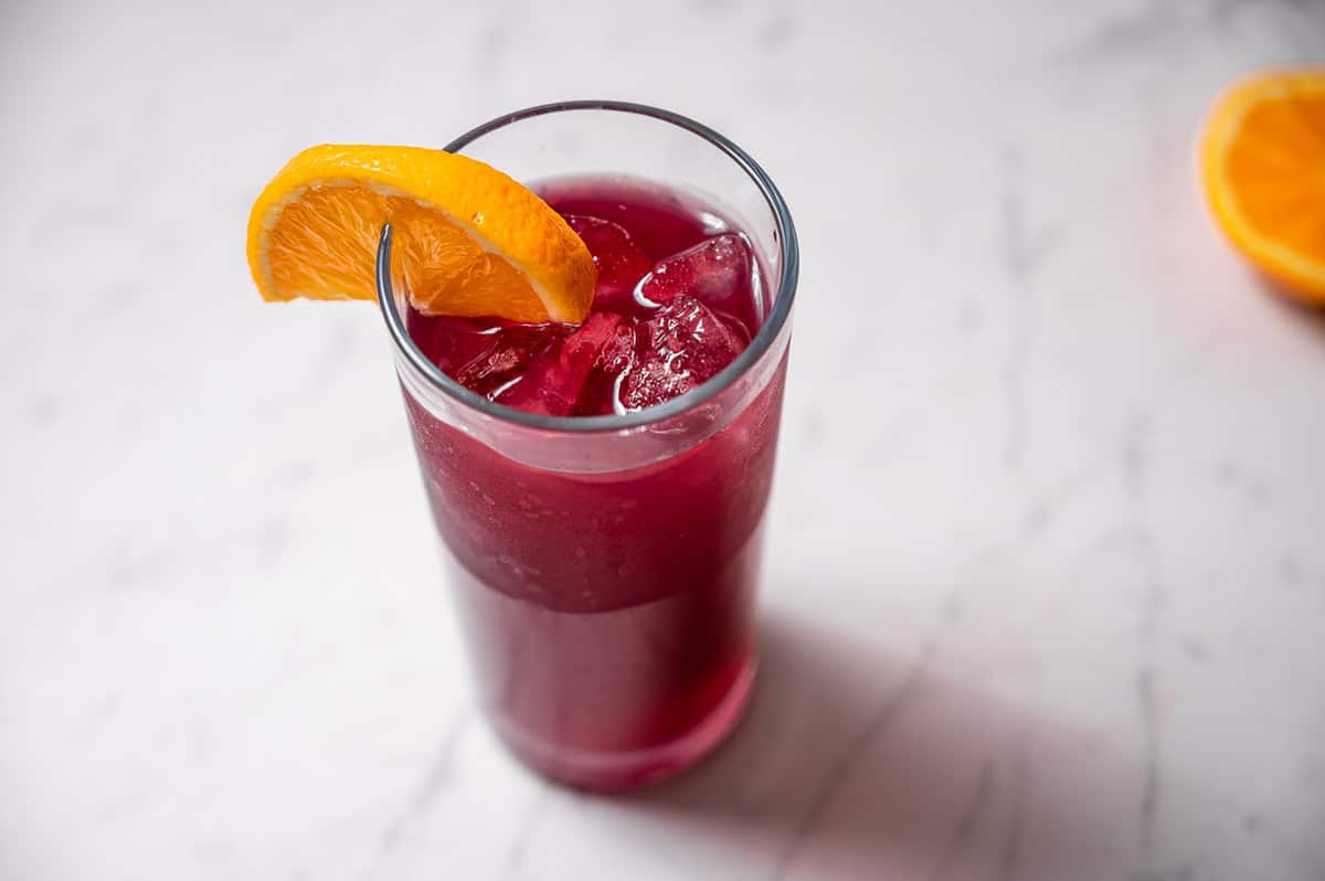 A tall glass of tinto de verano with an orange slice on the rim.