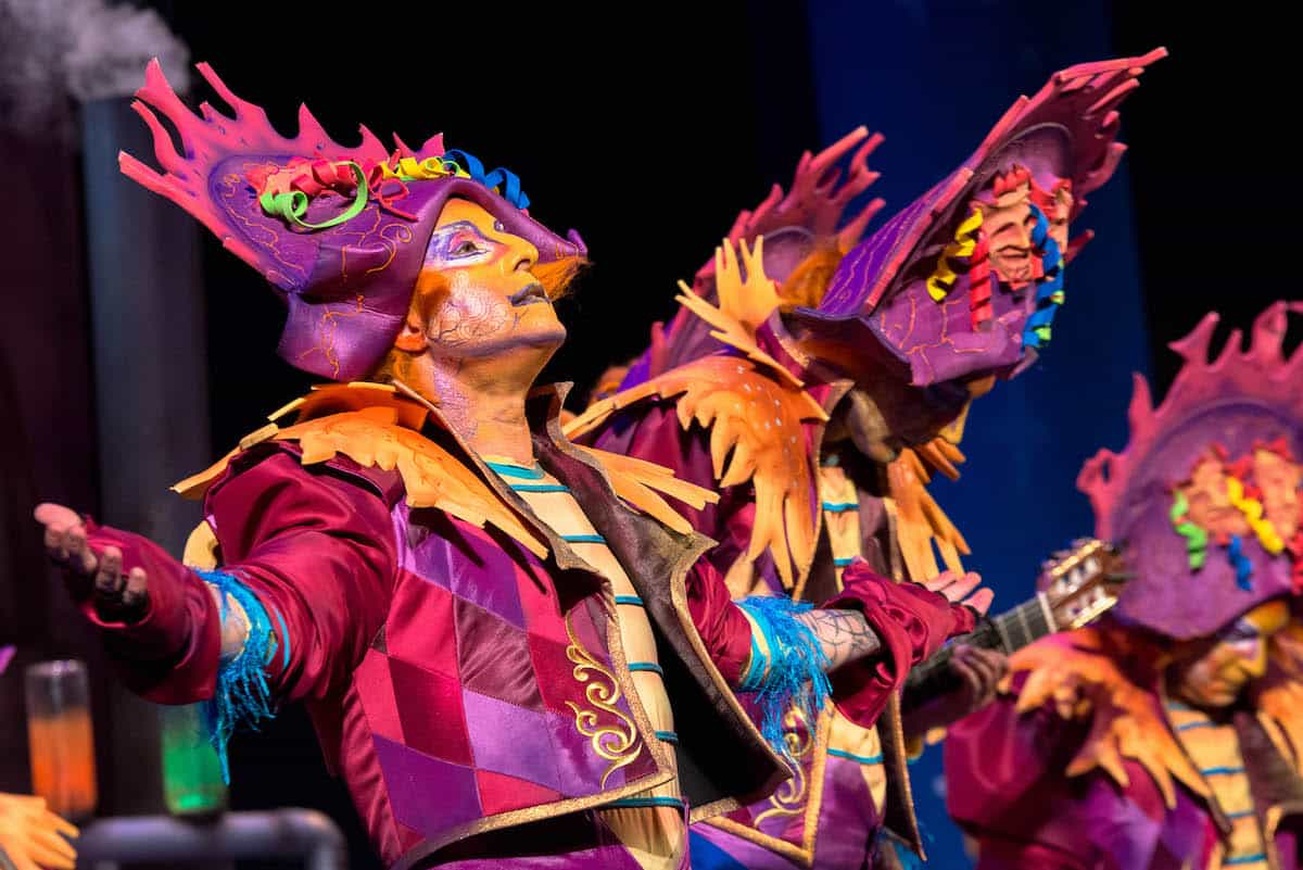 Performers in colorful costumes and makeup sing and dance at Carnival in Cadiz, Spain