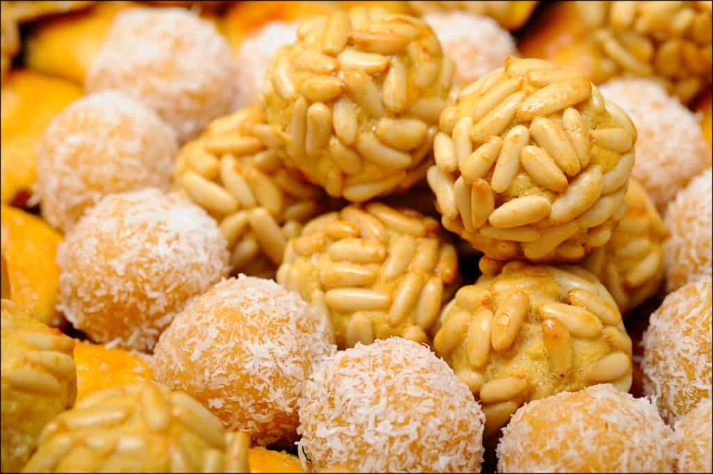 Array of marzipan sweets covered in pine nuts