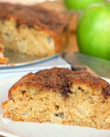 Close up of a slice of apple olive oil cake with the rest of the cake in the background