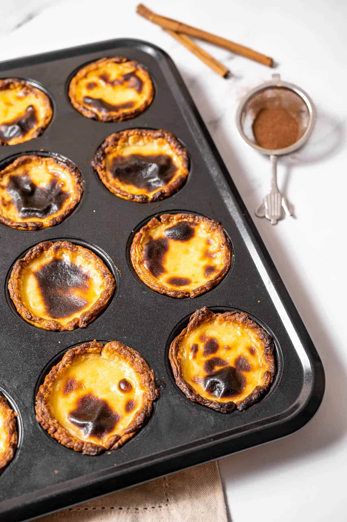 Portuguese Custard tarts in a baking tray with cinnamon in the background.