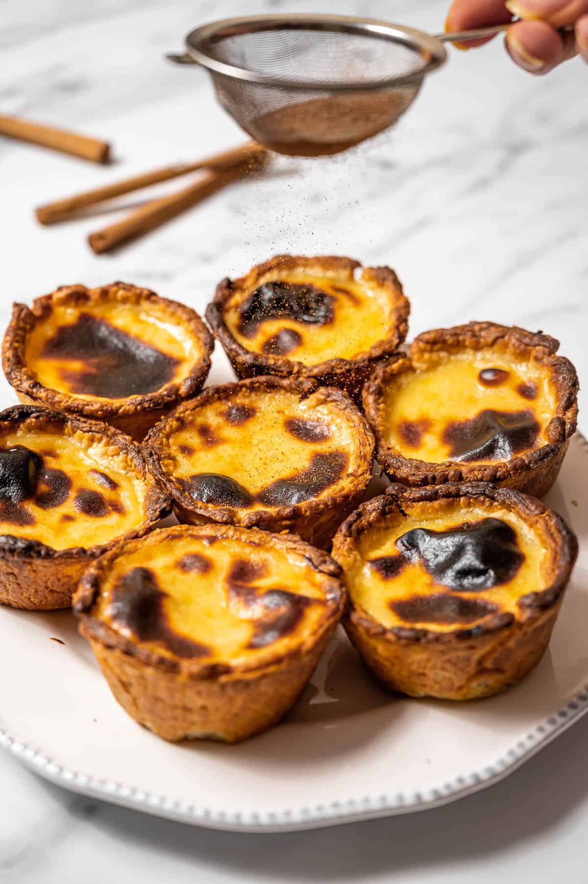 A plate of pasteis de nata (Portuguese custard tarts) with a sifter of ground cinnamon above