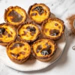 Pasteis de nata o na white plate with a sifter of cinnamon on the side.