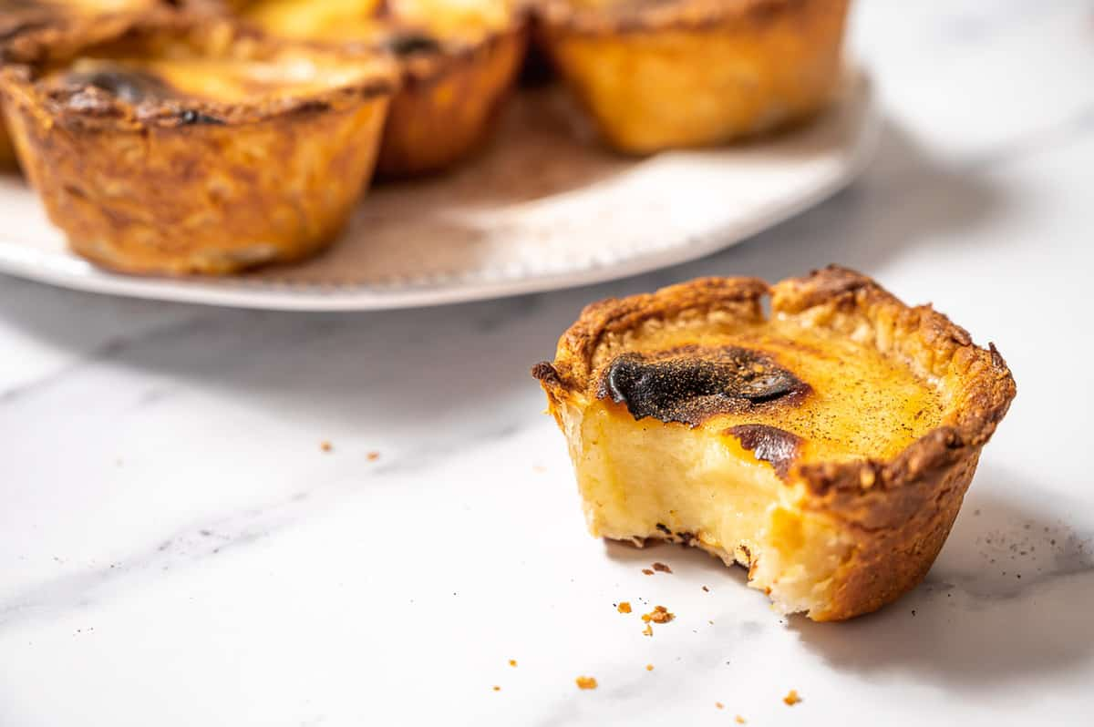A pastel de nata with a bite taken out of it, showing the creamy custard inside.