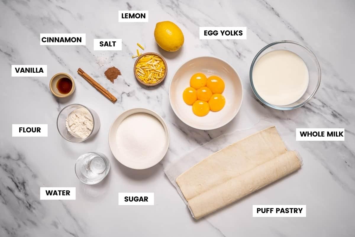 Ingredients to make pasteis de nata or custard tarts on a white marble countertop