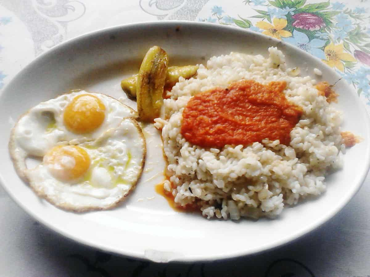 Plate of fried eggs, fried plantains, and rice topped with tomato sauce.