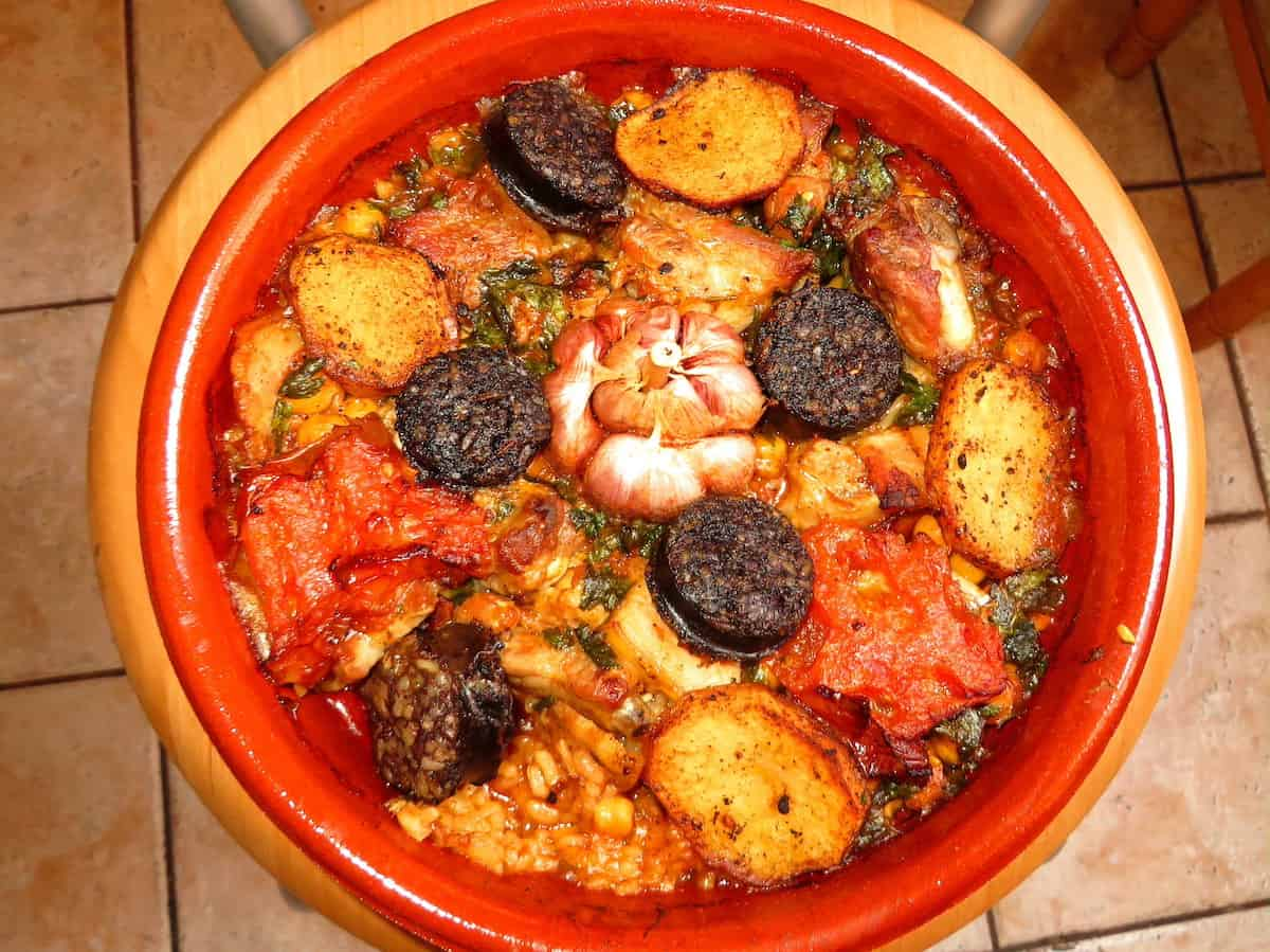 Overhead shot of baked rice with black pudding and garlic in a round dish.