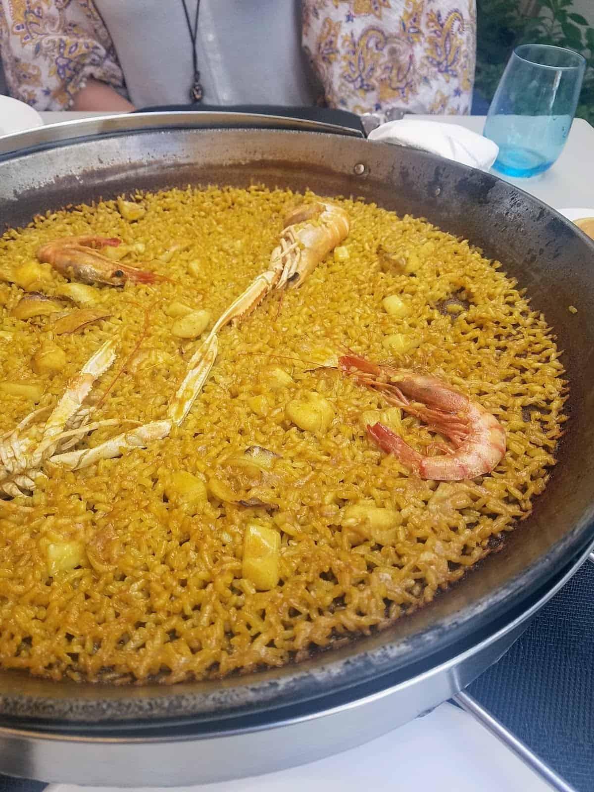 Large metal pan of seafood paella topped with shellfish.