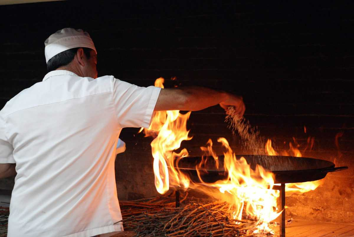 Chef cooking paella on an open flame