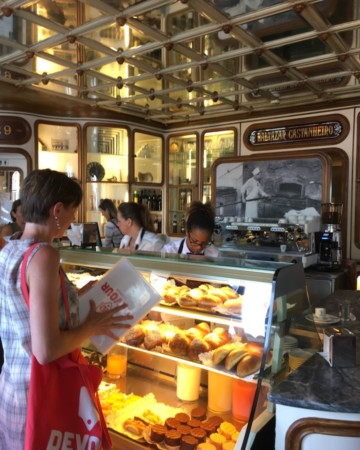 Ordering pastries and coffee on a food tour in Lisbon.