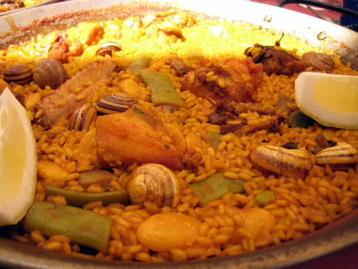 Close up of a pan of paella with lemon wedges, meat, beans, and snails.