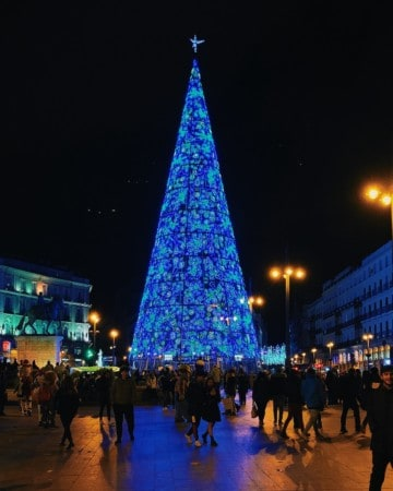 Large blue Christmas tree lit up at night in a busy city square