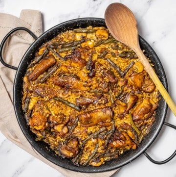 Overhead shot of a traditional Spanish paella with chicken and ribs in a black paella pan with a wooden spoon.