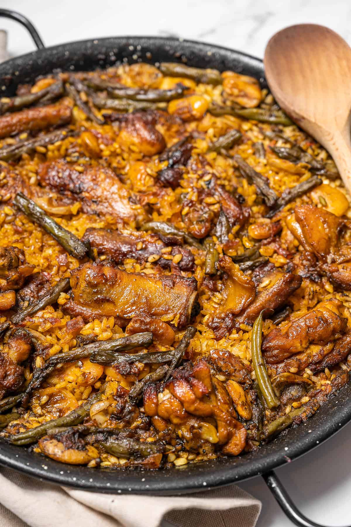 Paella Valenciana with chicken, ribs, and green beans. A traditional Spanish meat paella with a wooden spoon resting on top.