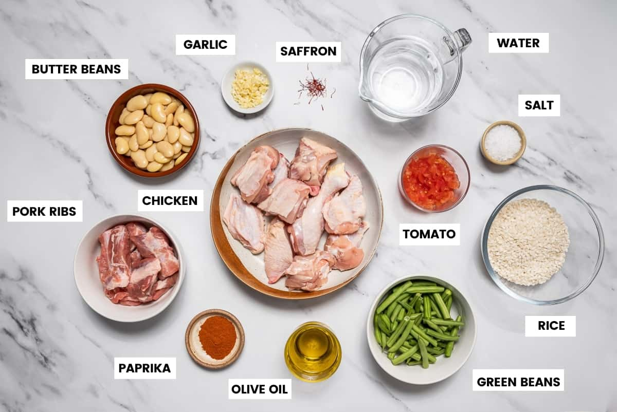 Ingredients to make Valencian paella on a white marble countertop.