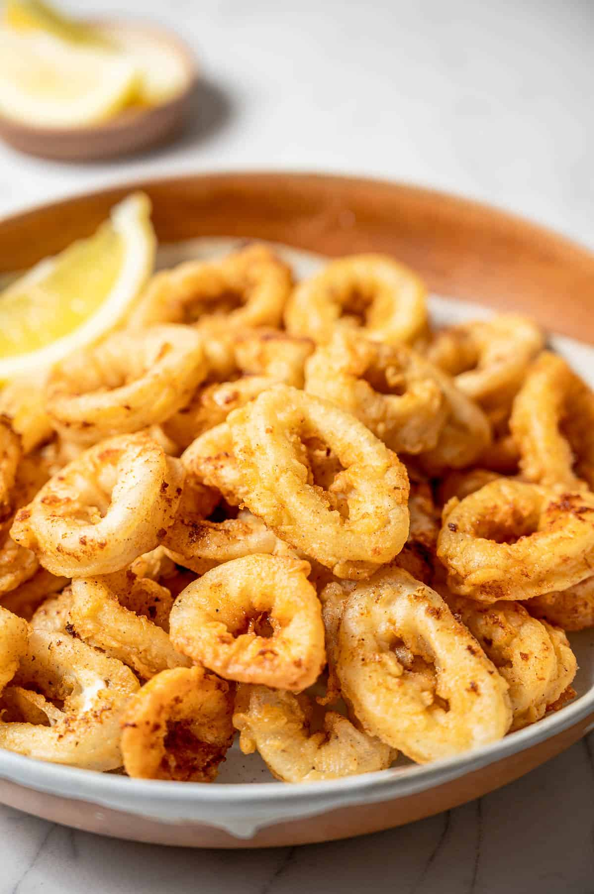 A bowl of fried calamari rings with lemon wedges