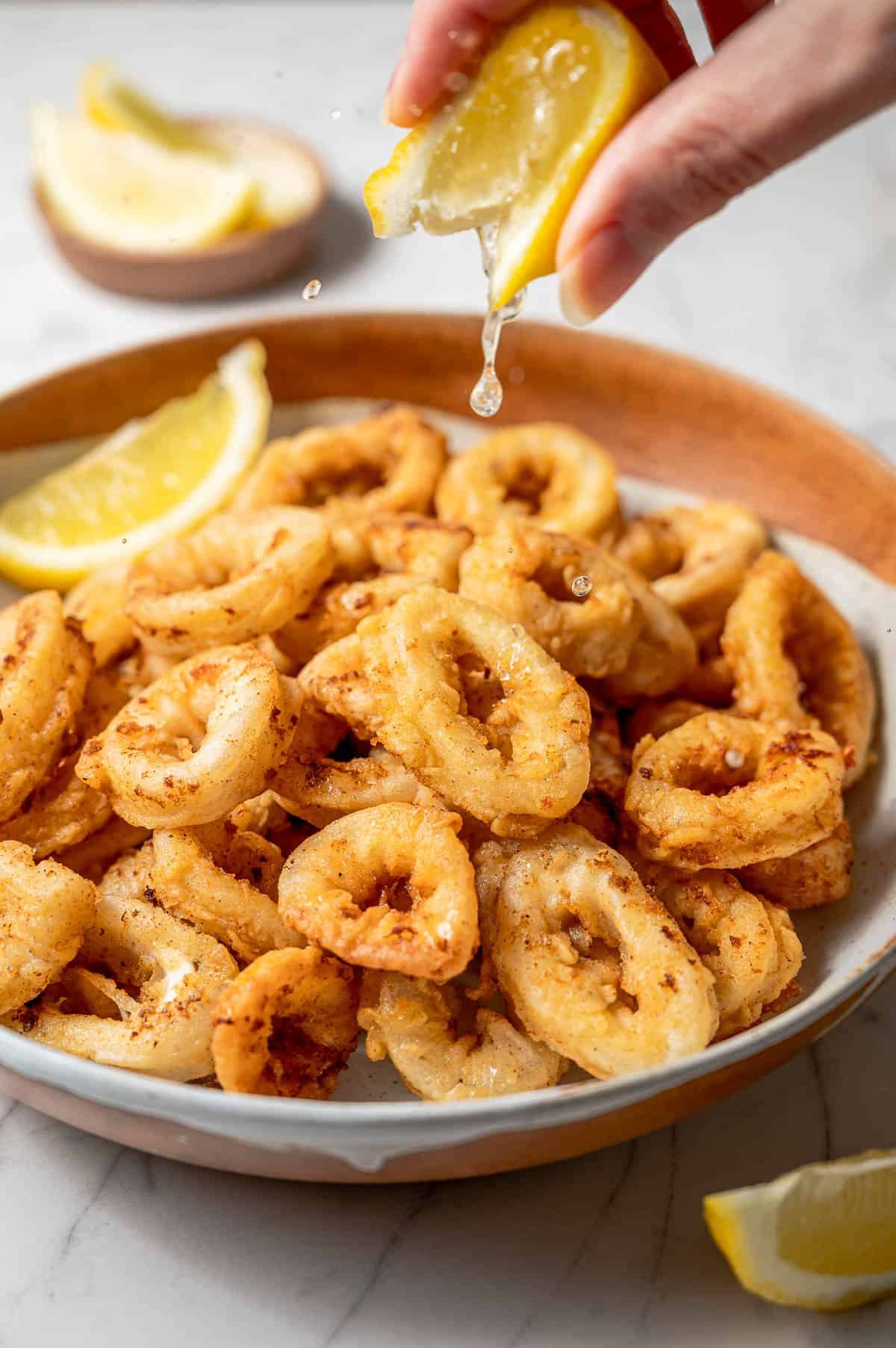 A large bowl of fried calamari with a hand squeezing lemon on top.