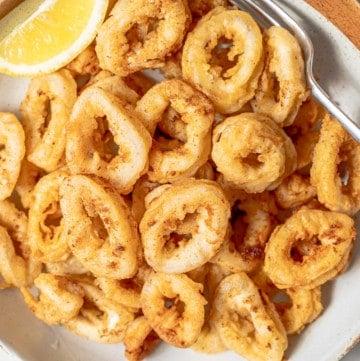 A big plate of fried calamari with a lemon wedge.