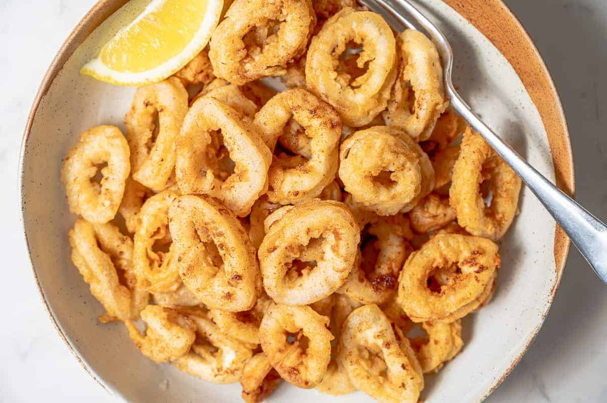 A big plate of fried calamari with a lemon wedge.