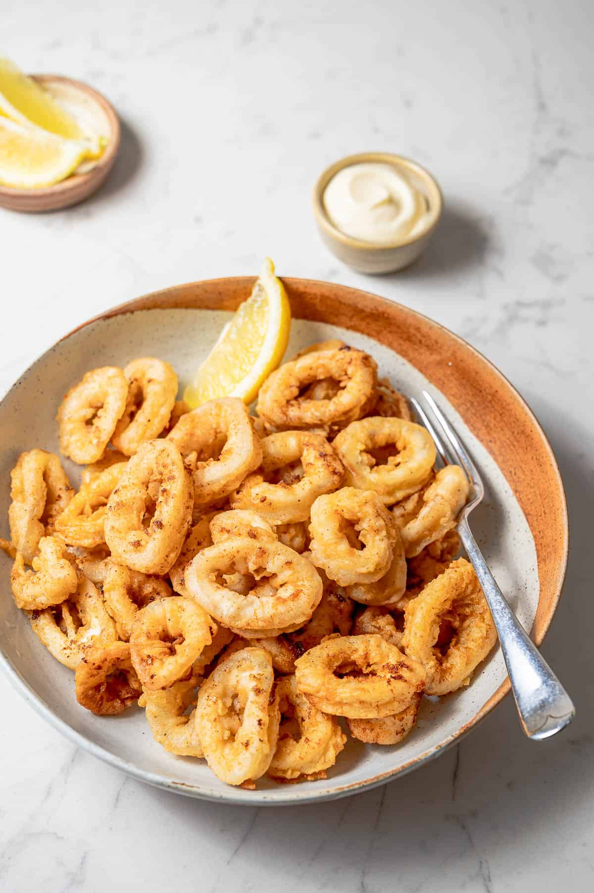 Bowl of fried calamari with lemon wedges and alioli sauce in a small bowl.