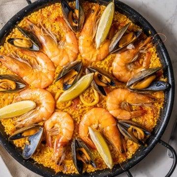 Overhead shot of seafood paella in a black paella pan with calamari, mussels, shrimp and lemons.