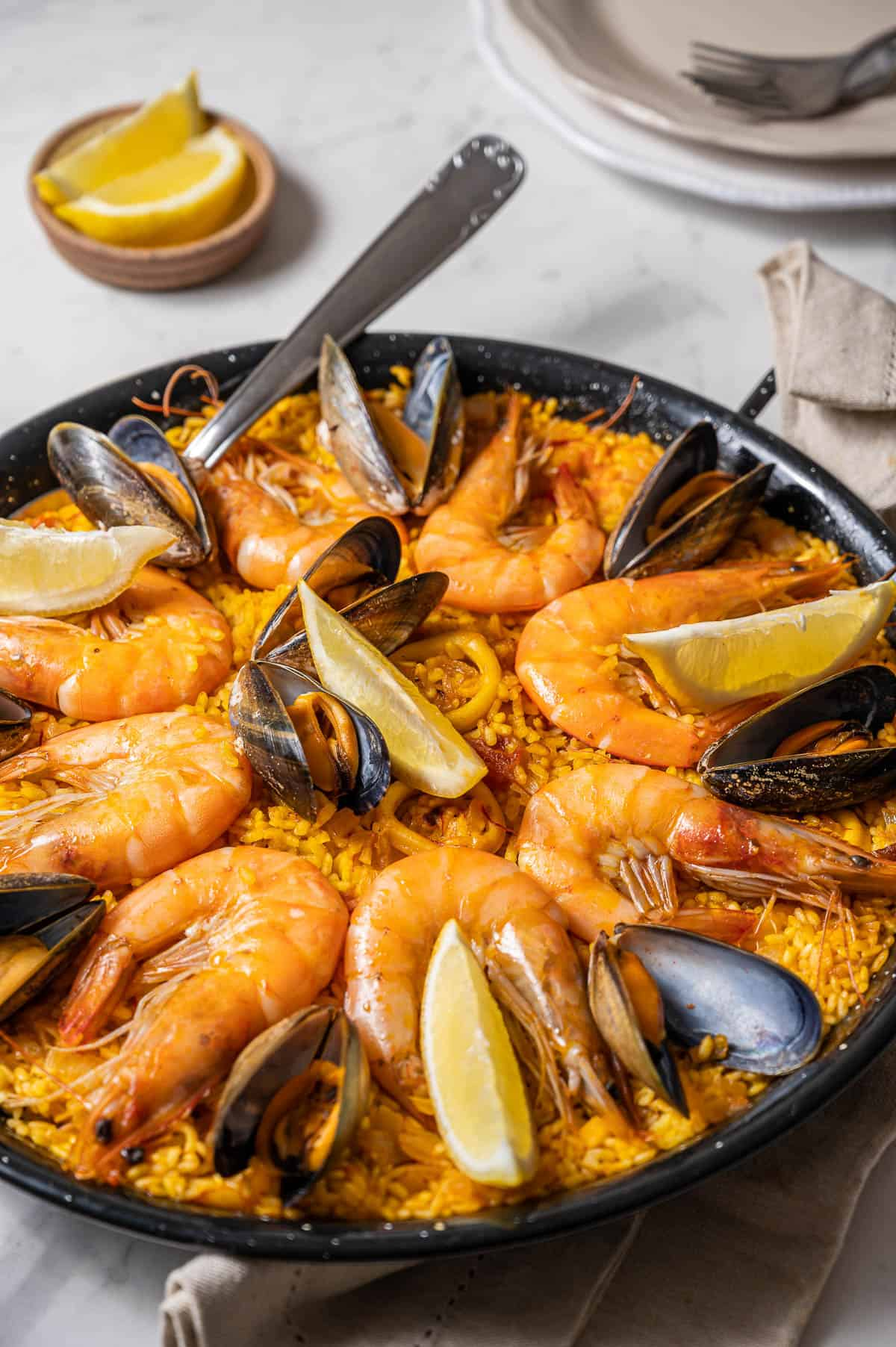 Seafood paella with prawns, mussels, calamari and lemon slices