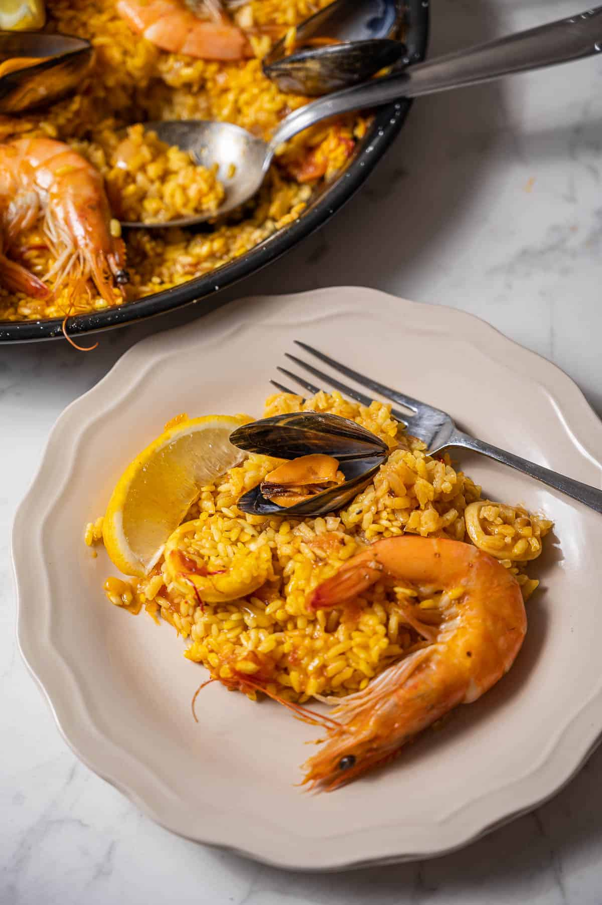 Serving of seafood paella on a white plate in front of the rest of the paella in the pan