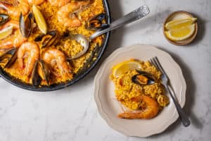 One serving of paella on a white plate with the rest of the paella pan in the background and some lemon wedges on the side.