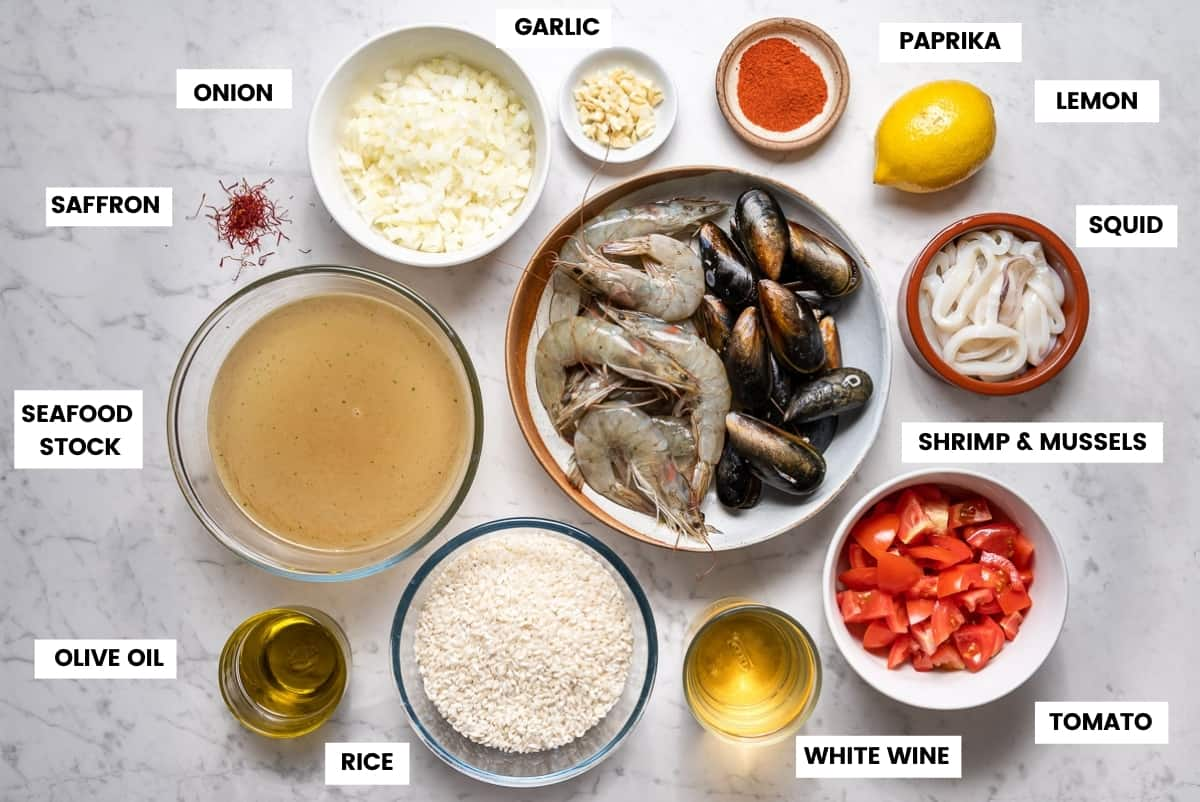 Ingredients for seafood paella laid out in small bowls on a white marble countertop.