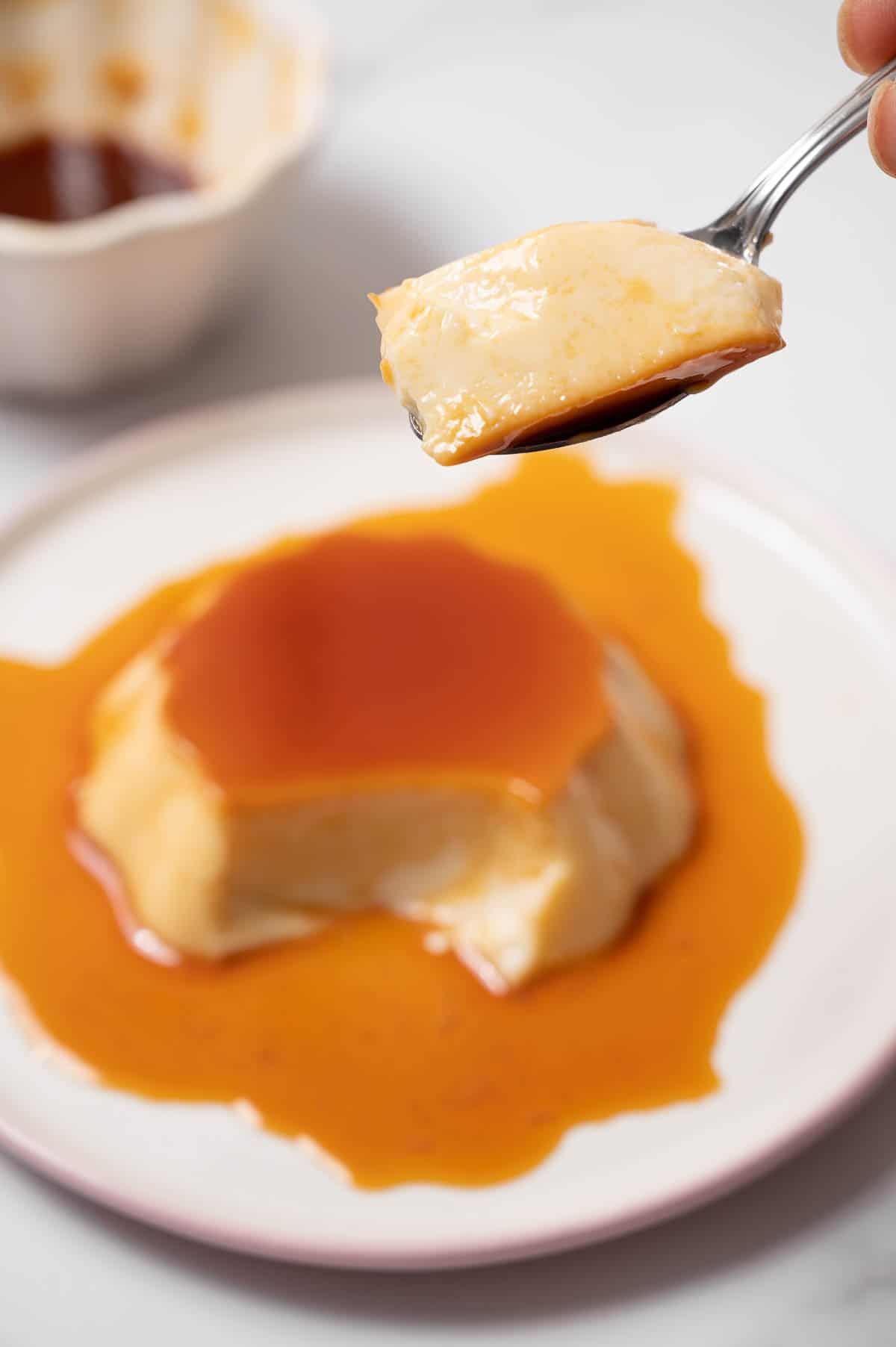 Bite of Spanish flan on a spoon