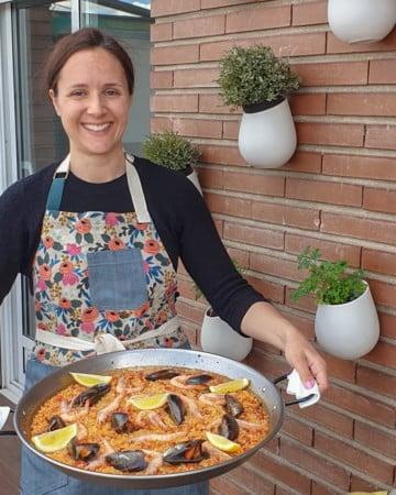 Woman holding a large pan of seafood and chorizo paella.